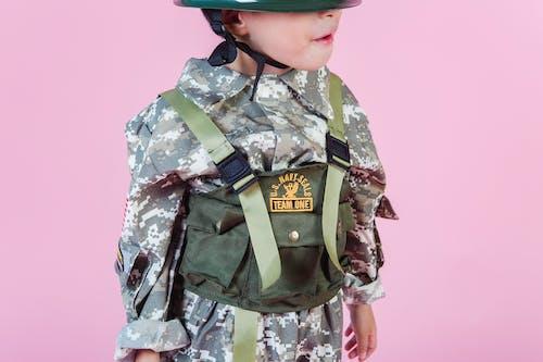Crop kid wearing military costume and helmet