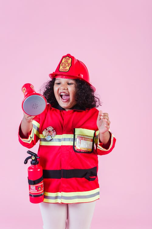 Joyful little African American girl wearing bright red firefighter costume and helmet playing with toy loudspeaker in light studio