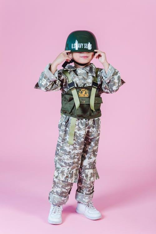 Cute kid wearing military costume and helmet
