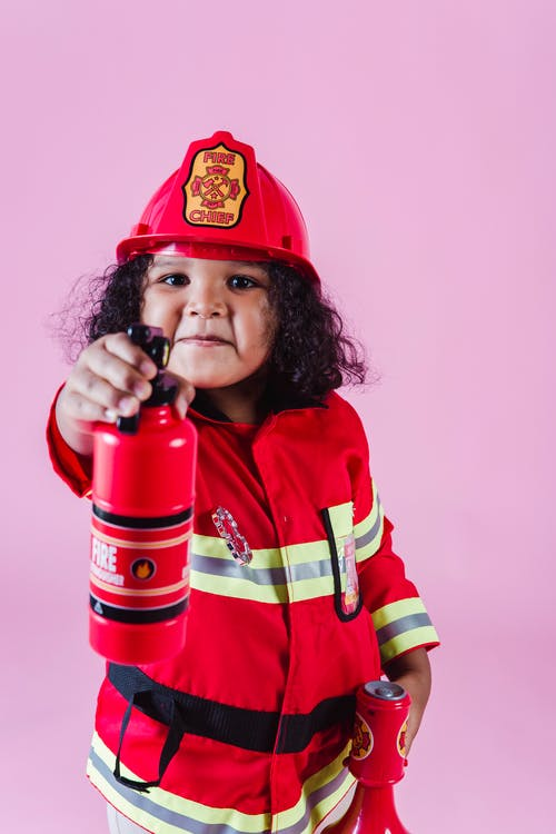 Adorable content little African American girl in bright red firefighter costume pointing toy fire extinguisher at camera while playing in light studio
