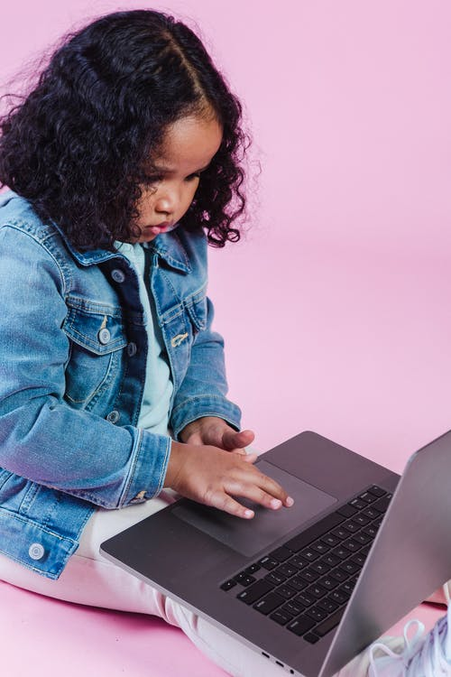 Cute concentrated African American girl wearing casual clothes using modern netbook while sitting on floor on pink background