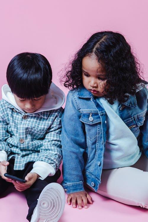 Focused diverse kids browsing smartphone on floor