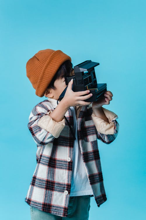 Unrecognizable little boy in stylish clothes and hat taking photos on instant film photo camera against blue wall in studio