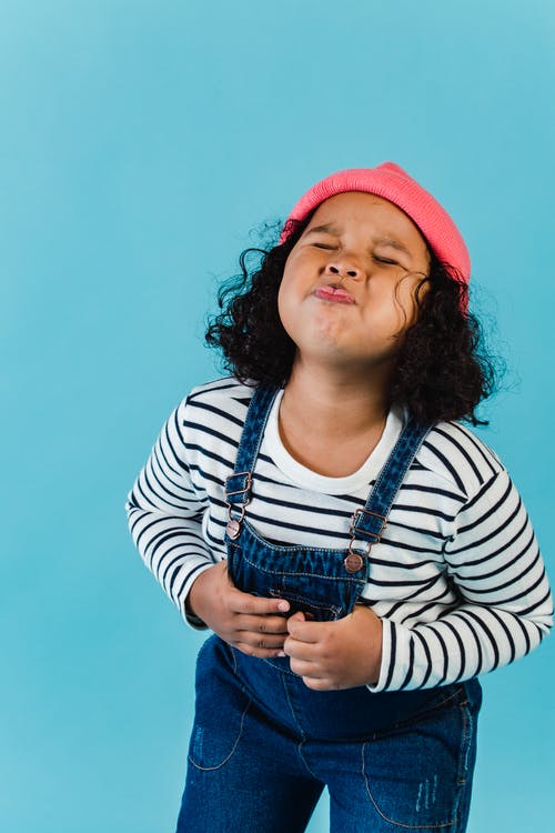 Cute happy African American girl in denim jumpsuit puffing cheeks and grimacing while standing with eyes closed against blue background