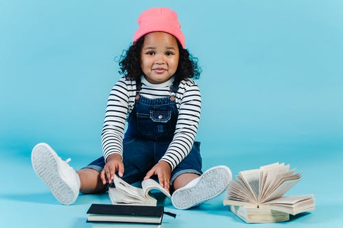 Cheerful black girl sitting on floor with many books