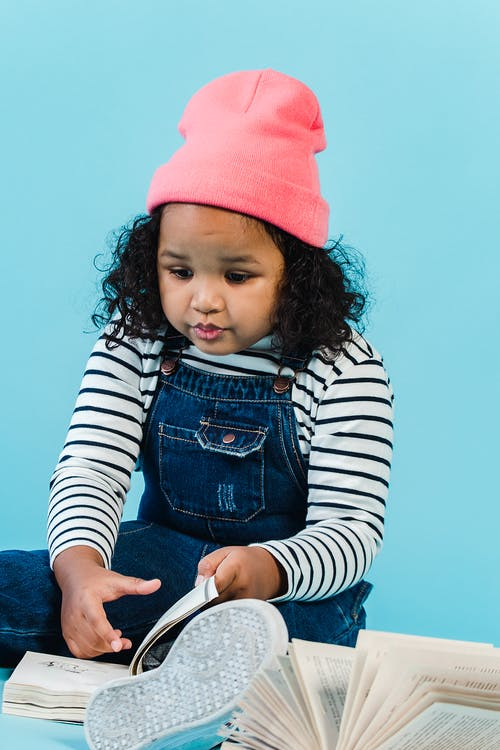 Cute little African American girl in denim jumpsuit and pink hat reading interesting book and sitting on floor against blue wall
