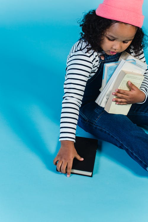 Black girl with books sitting on floor