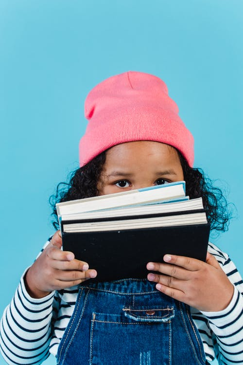 Cute little African American girl in trendy clothes covering face with stacked books and looking at camera while standing against blue wall