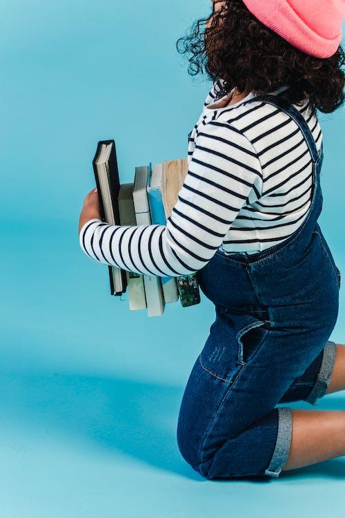 Vrouw In Wit En Zwart Gestreept Shirt Met Lange Mouwen En Blue Denim Jeans Holding Book