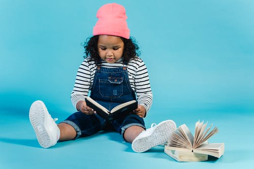 Full body focused little African American girl in trendy outfit reading interesting story and sitting on floor against blue background