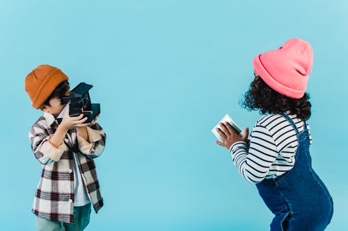 Faceless boy taking picture of girl with curly hair