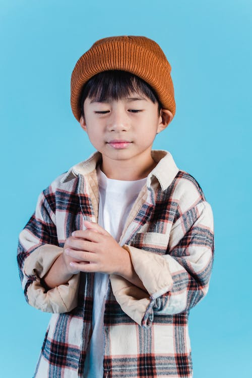 Cute stylish Asian boy standing in studio