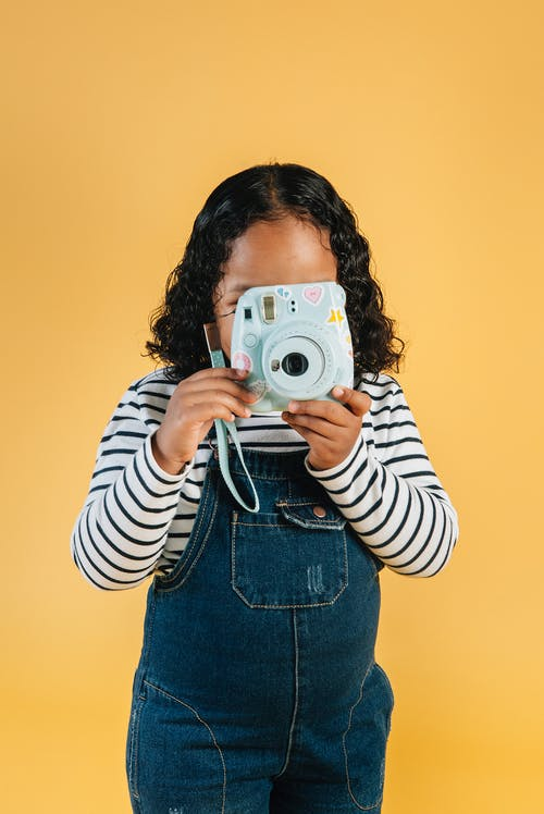 Unrecognizable little stylish ethnic girl in denim jumpsuit taking photo on contemporary instant photo camera while standing against brown background