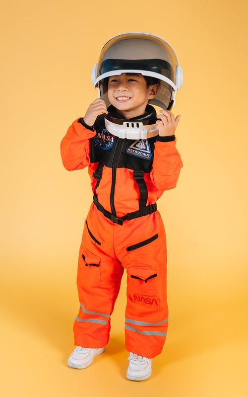 Full body joyful little Asian boy in orange astronaut spacesuit and helmet while standing against brown background and looking away with happy smile
