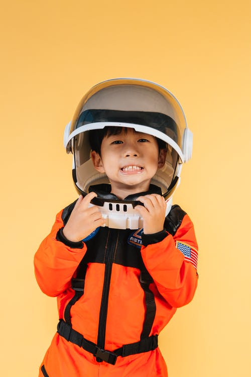 Garçon En Veste Zippée Orange Et Noire Portant Un Casque Blanc