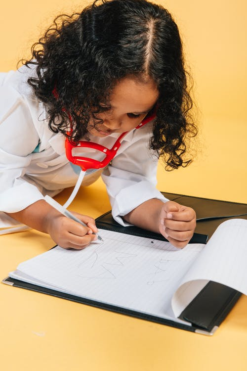 Crop black girl playing doctors game and writing in notebook