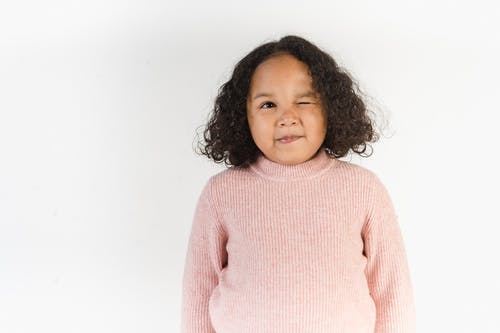 Adorable African American kid winking at camera in white studio