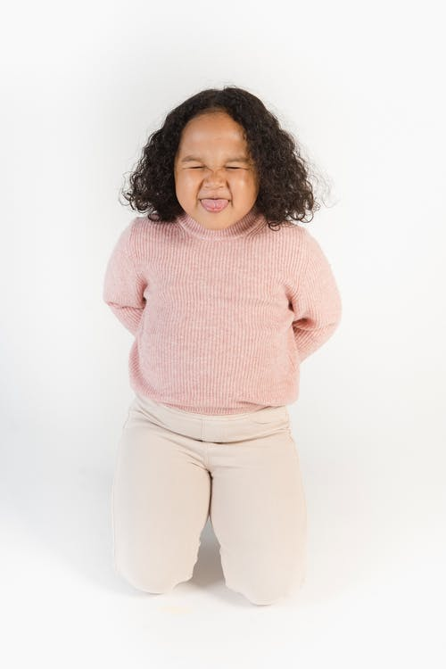 Cheerful adorable little African American girl sitting on knees with hands behind back and showing tongue with closed eyes while playing against white background
