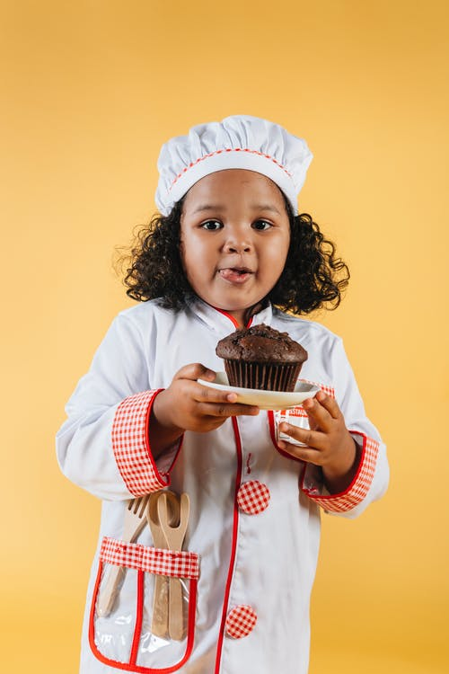Girl in White and Red Polka Dot Long Sleeve Shirt Holding Chocolate Cupcake