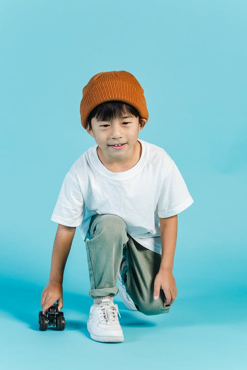 Content Asian boy playing with toy car in studio
