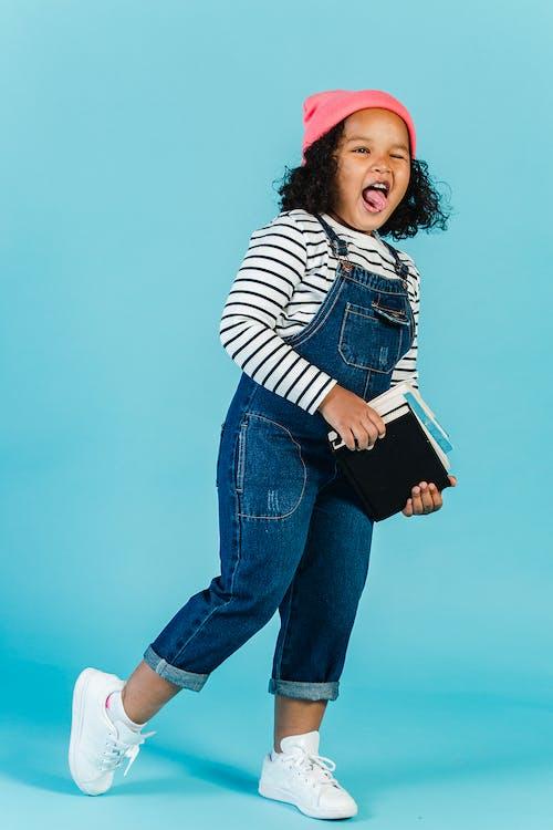 Joyful black girl with textbooks grimacing in studio