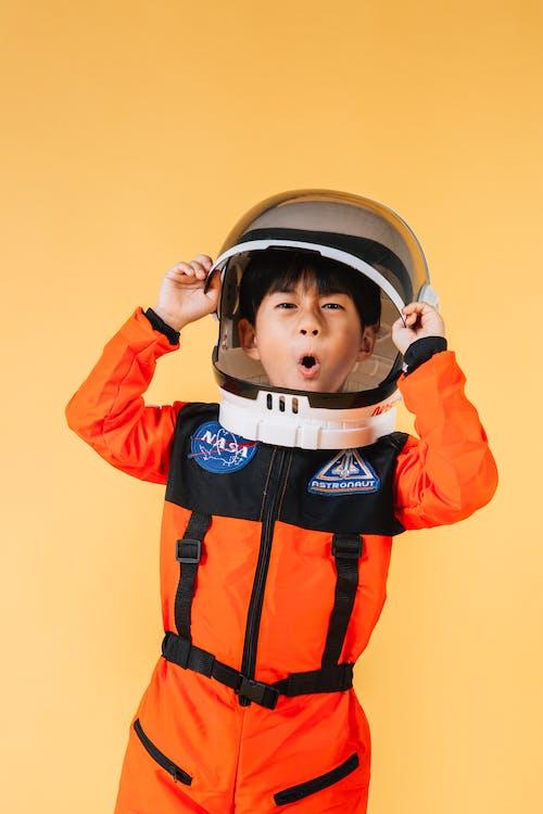 Boy in Orange and Black Zip Up Jacket Wearing White Helmet