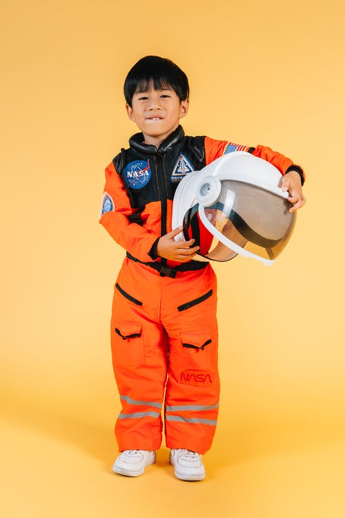 Full length positive little Asian boy in cosmonaut costume biting lip and holding spaceman helmet while standing on yellow background and looking at camera