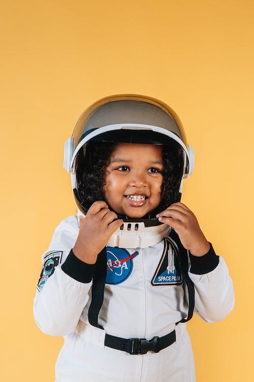 Smiling black girl wearing cosmonaut suit and touching helmet