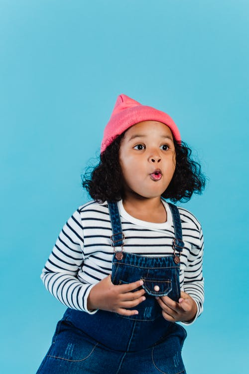 Cute amazed African American girl in cool outfit and pink hat staring away with astonishment while standing on blue background