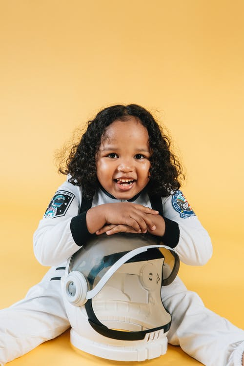 Happy little African American girl wearing astronaut costume and looking at camera with smile while sitting on floor and leaning on helmet against yellow background