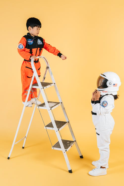 Little ethnic children in cosmonaut costumes playing on ladder