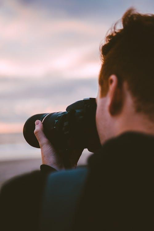 Man in Black Jacket Holding Black Dslr Camera during Sunset