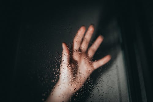 Persons Left Hand on Glass With Water Droplets