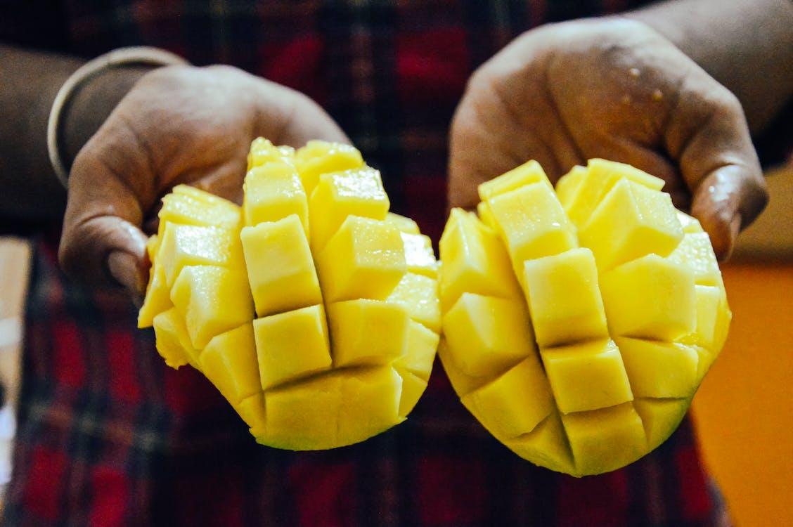 Ethnic person showing bright cut mango