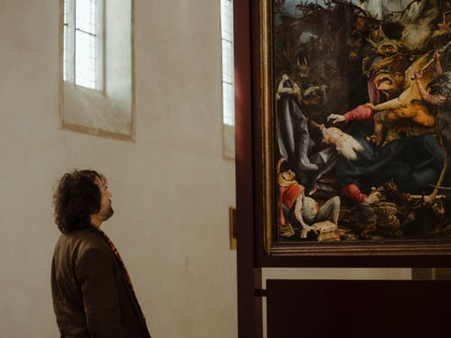 Man watching painting in classic art gallery