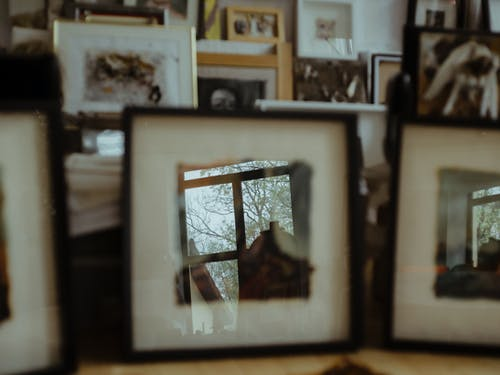 Interior of light room with oodles frames on table and wall decorated with picture