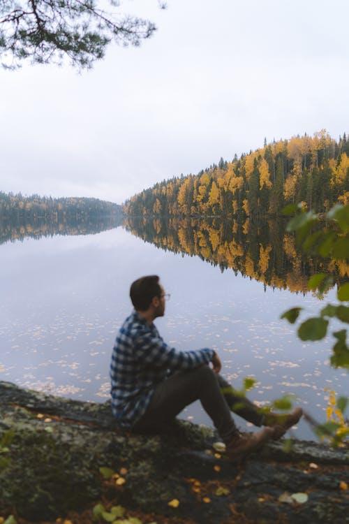 Man in Black and White Checkered Dress Shirt Sitting on Brown Wooden Log Near Body of Near Near Near Near