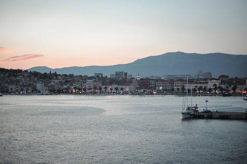 Calm sea harbor near city and mountain