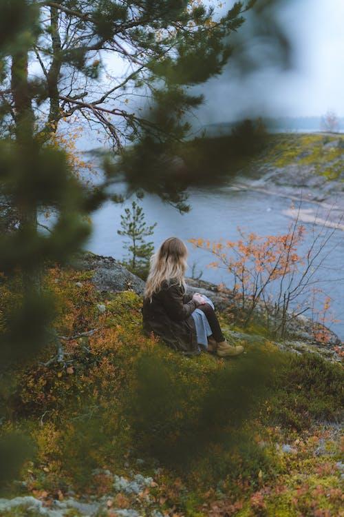 Woman in Black Jacket Sitting on Green Grass Near Body of Water