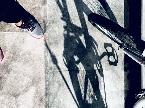 Free stock photo of bicycle, healthy lifestyle, shadow, sneakers