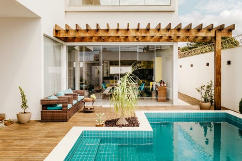 Modern lounge zone with swimming pool on terrace of modern villa in sunny day