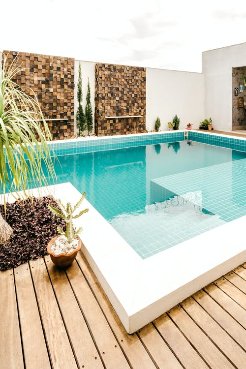 Comfortable lounge zone with swimming pool with clear water on terrace of modern villa in daytime
