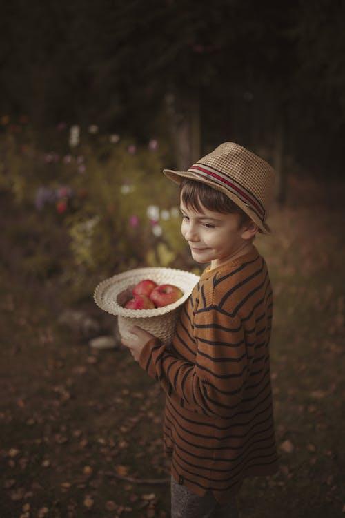 Content boy with hat of apples standing in garden