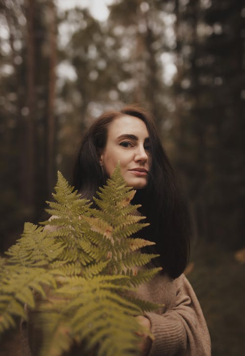 Positive woman with fern leaves standing in lush forest