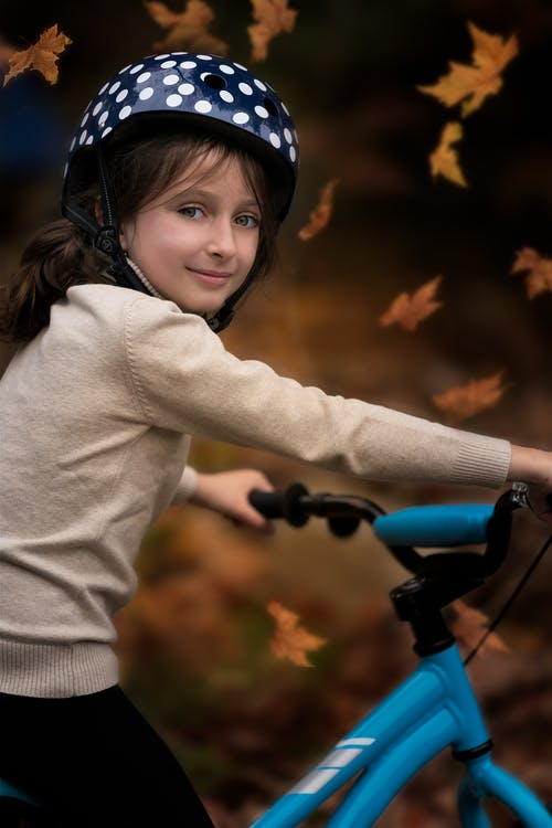Content girl in helmet and sweater riding bicycle in autumn park and looking at camera
