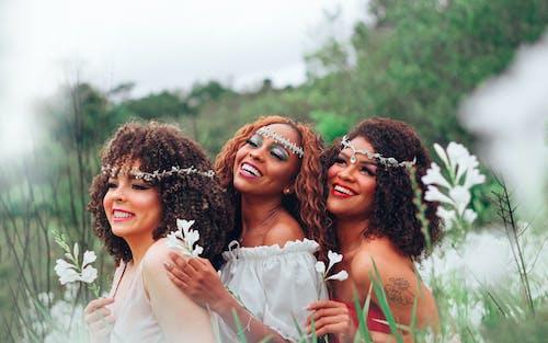 Happy multiethnic women in blooming field
