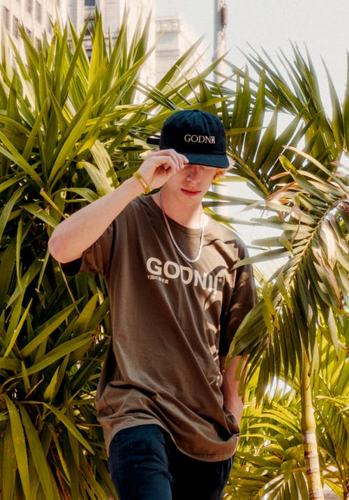 Man in Black Crew Neck T-shirt and Blue Fitted Cap Standing Near Green Plants during