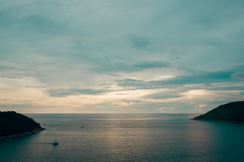 Sailboats on endless ocean between ridges in evening
