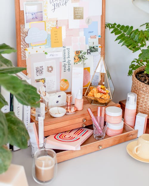 Wooden cosmetic box with various products placed on white table with houseplants and books