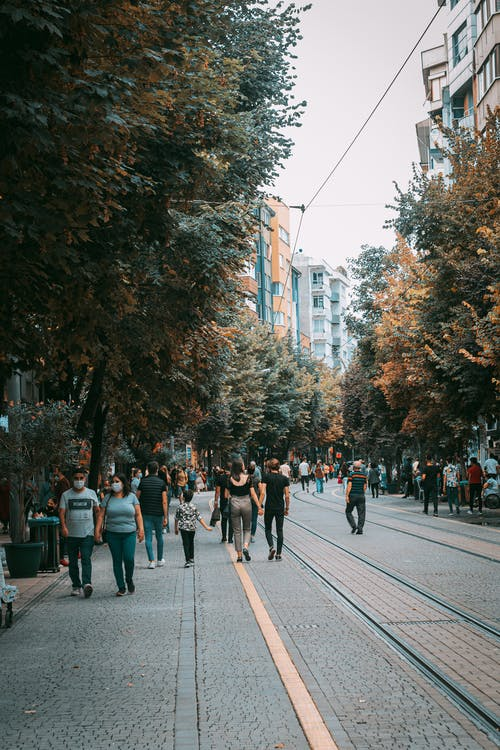 People Walking on Sidewalk Near High Rise Buildings